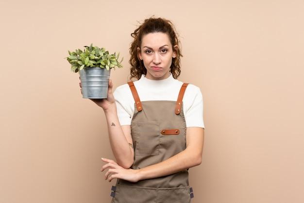 Donna del giardiniere che tiene una pianta con l'espressione triste