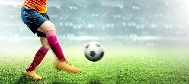 Donna del giocatore di football americano in maglia arancio che dà dei calci alla palla