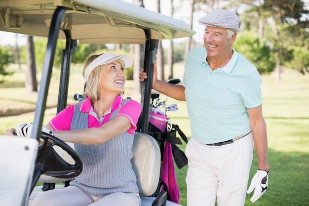 Donna del giocatore di golf che esamina uomo mentre sedendosi nel buggy di golf
