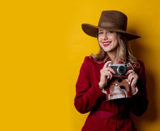 Donna del giornalista in cappello con la macchina fotografica