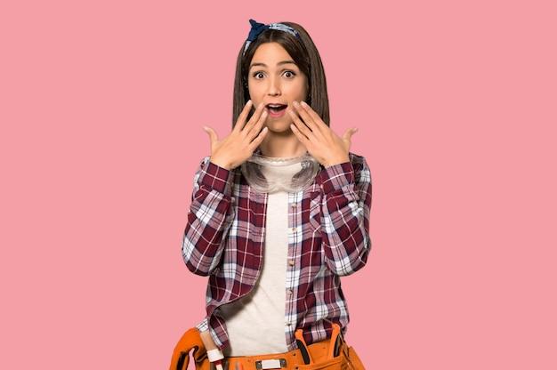Donna del giovane operaio con espressione facciale di sorpresa sulla parete rosa isolata