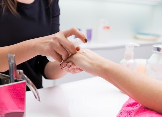 Donna del manicure del salone del chiodo che applica crema per le mani