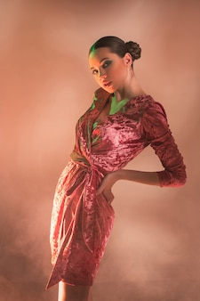 Donna del modello di alta moda nella posa variopinta delle luci intense