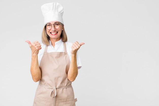 Donna del panettiere di mezza età che sorride con gioia e che sembra felice, sentendosi spensierata e positiva con entrambi i pollici contro la parete piatta