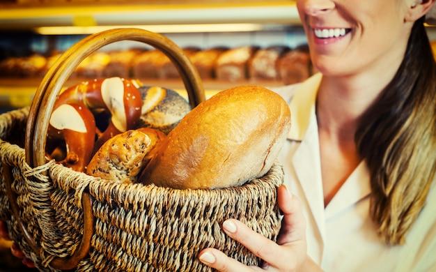 Donna del panettiere nel sostenitore che vende la merce nel carrello del pane