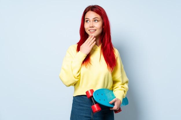 Donna del pattinatore dell'adolescente isolata sulla parete bianca che cerca mentre sorridendo