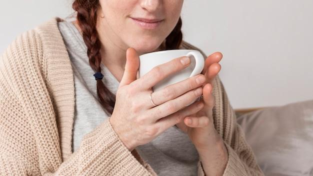 Donna del primo piano che beve tè caldo