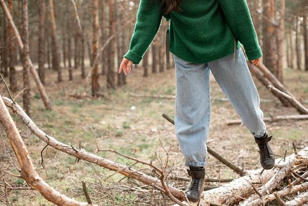 Donna del primo piano che cammina sull'albero caduto