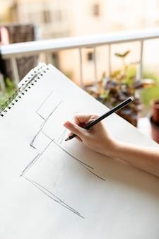 Donna del primo piano che disegna con la matita