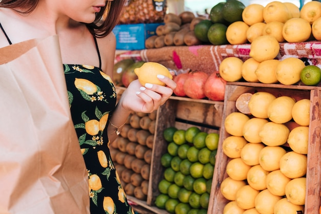 Donna del primo piano che esamina i limoni