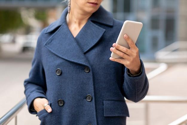 Donna del primo piano che esamina smartphone