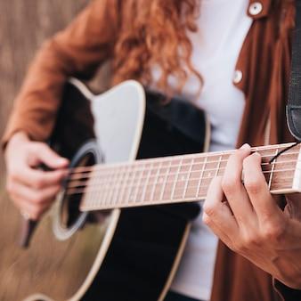 Donna del primo piano che gioca chitarra