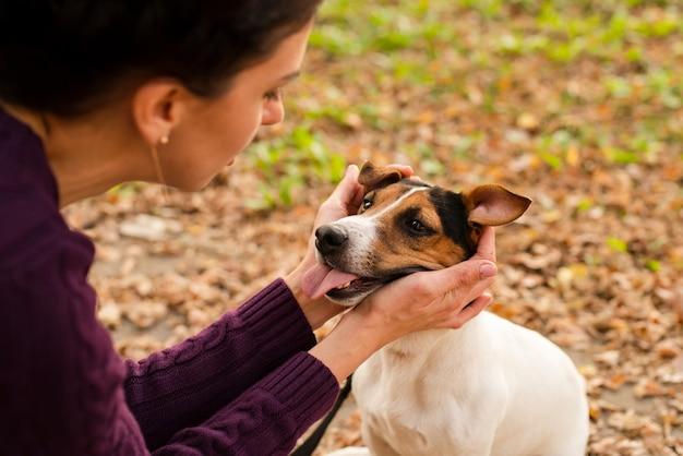 Donna del primo piano che gioca con il suo cane