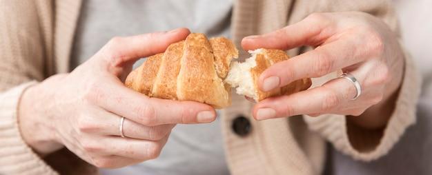 Donna del primo piano che gode del croissant