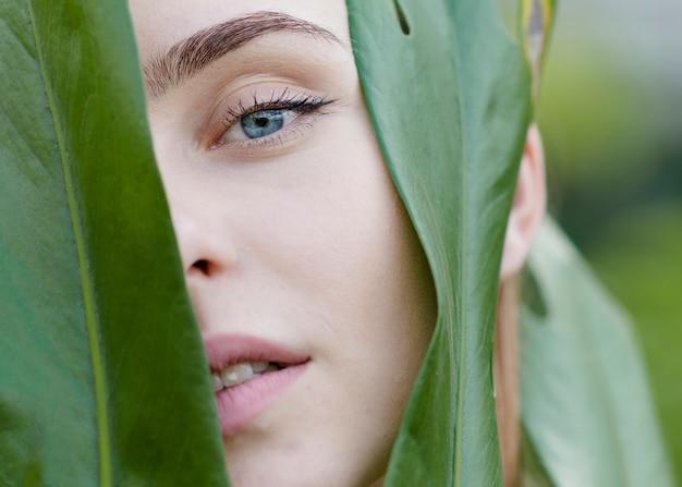 Donna del primo piano che guarda tramite le foglie