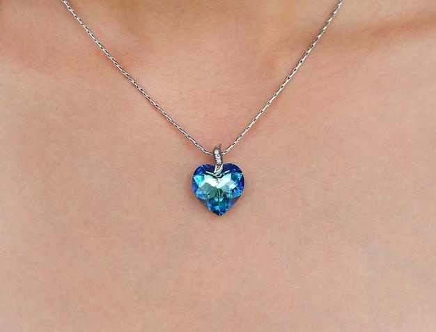 Donna del primo piano che indossa la collana di cristallo brillante del cielo blu