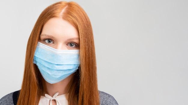 Donna del primo piano che indossa maschera medica
