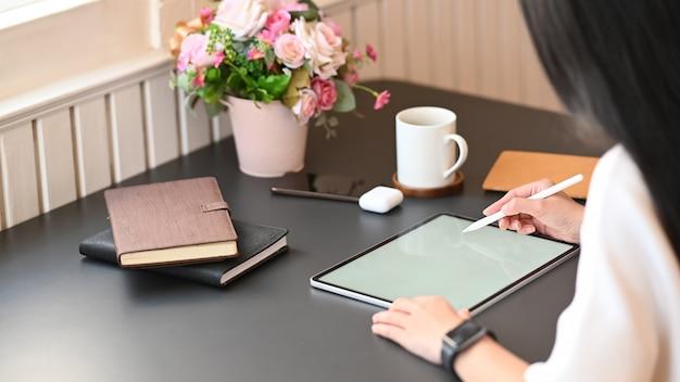 Donna del primo piano che lavora come grafico che attinge la compressa bianca del computer dello schermo in bianco mentre sedendosi al tavolo di lavoro moderno con il salone comodo as