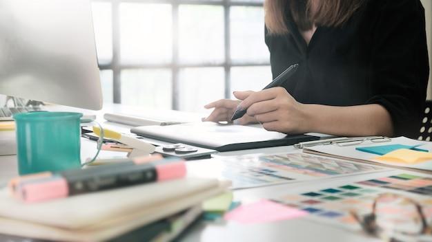 Donna del primo piano che lavora con lo schizzo sulla tavola digitale, grafico che lavora al tavolo.
