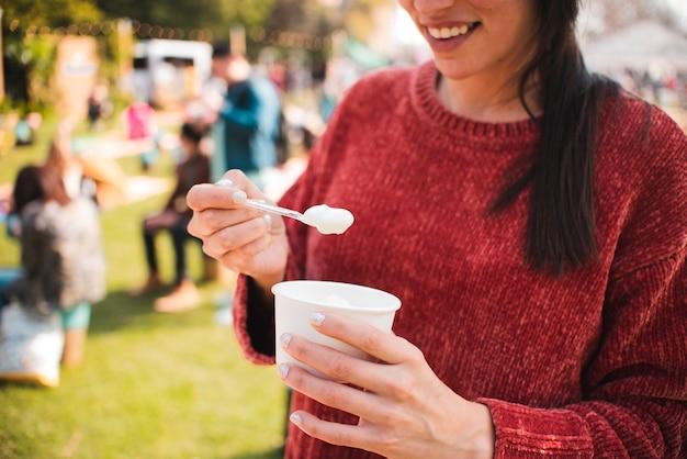Donna del primo piano che mangia il gelato con il cucchiaio