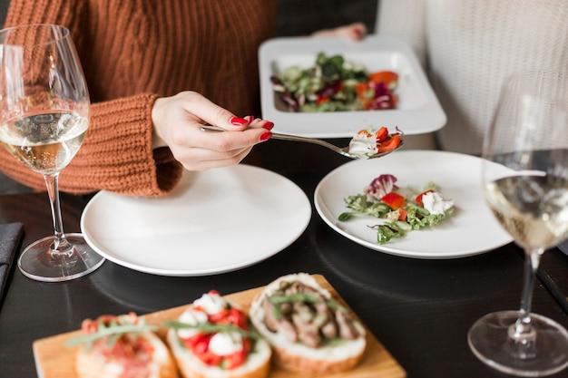 Donna del primo piano che mangia insalata e vino