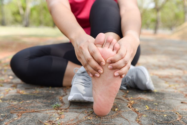 Donna del primo piano che massaggia il suo dolore del piede sul pavimento mentre si esercita. assistenza sanitaria e il concetto di sport.