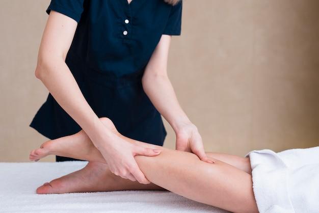 Donna del primo piano che massaggia le gambe del cliente