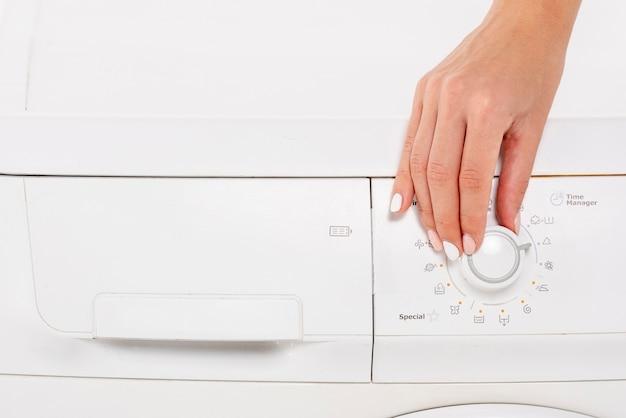 Donna del primo piano che mette la lavatrice