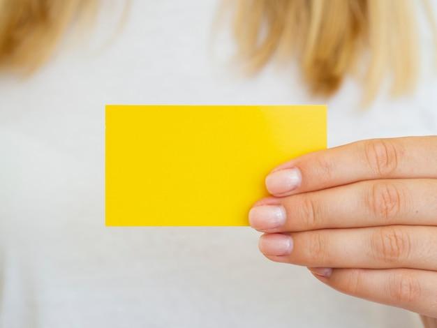Donna del primo piano che ostacola il biglietto da visita giallo