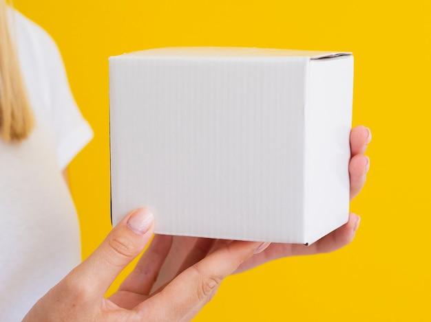 Donna del primo piano che ostacola piccola scatola
