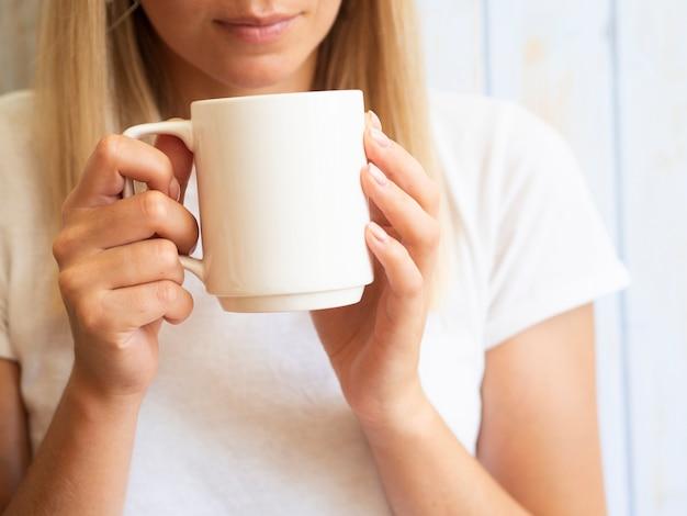 Donna del primo piano che ostacola tazza bianca