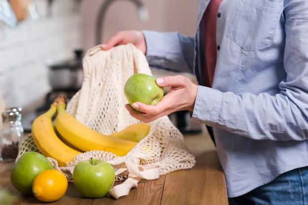 Donna del primo piano che ottiene frutti organici dalla borsa di eco