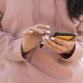 Donna del primo piano che per mezzo del suo telefono cellulare