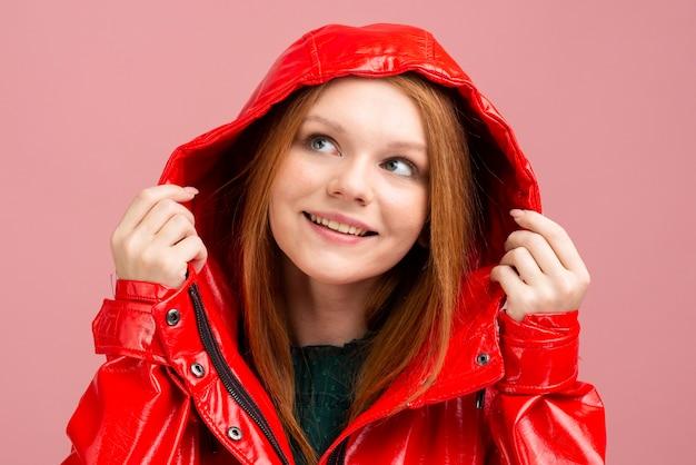 Donna del primo piano che porta la giacca di pioggia rossa