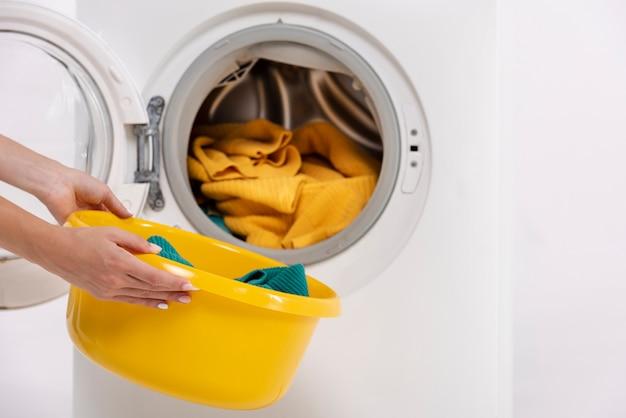 Donna del primo piano che prende i vestiti dalla lavatrice
