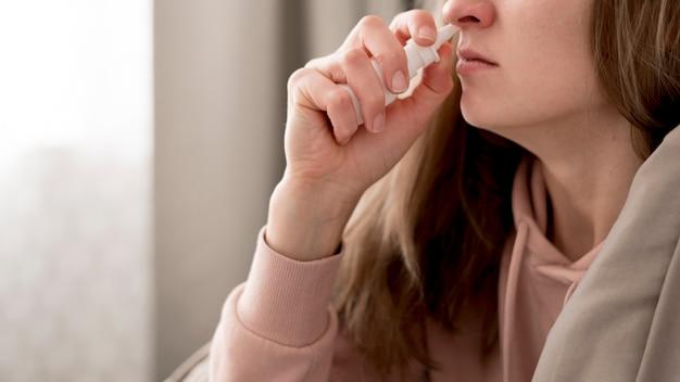 Donna del primo piano che prende trattamento per il naso che cola
