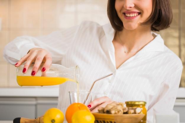 Donna del primo piano che prepara il succo di arancia