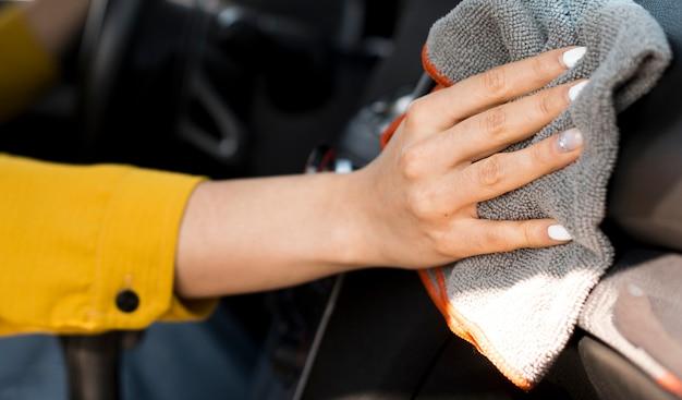 Donna del primo piano che pulisce l'automobile