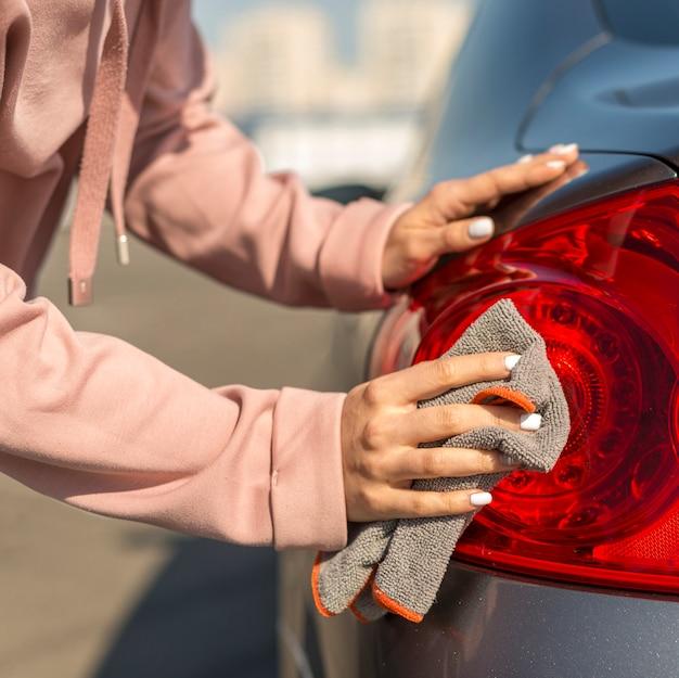 Donna del primo piano che pulisce la sua automobile all'aperto