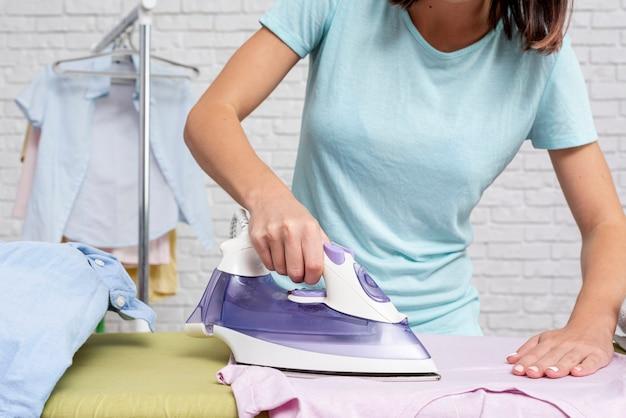 Donna del primo piano che riveste di ferro una camicia