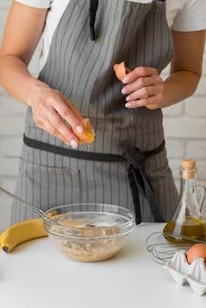 Donna del primo piano che rompe uovo sopra la ciotola