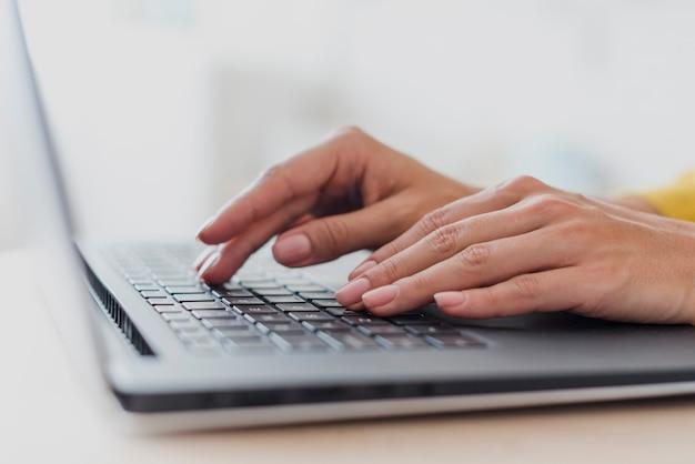 Donna del primo piano che scrive sulla tastiera del computer portatile