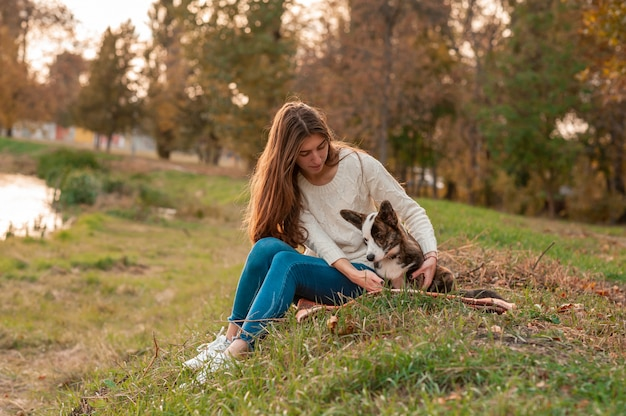 Donna del primo piano che si siede con il suo cane in foglie di autunno all'aperto