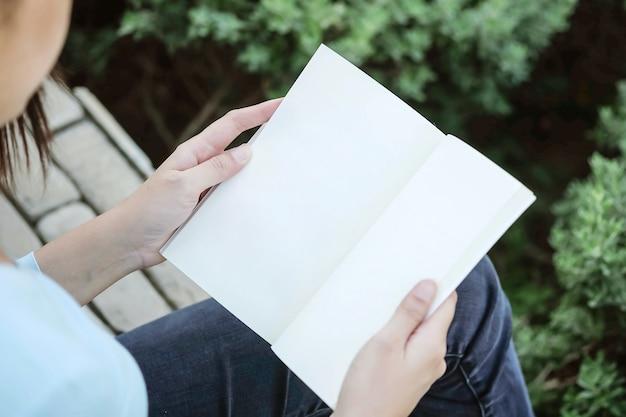 Donna del primo piano che si siede per la lettura del libro nel tempo libero nel giardino