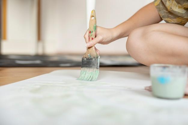 Donna del primo piano che si siede sul pavimento con la spazzola