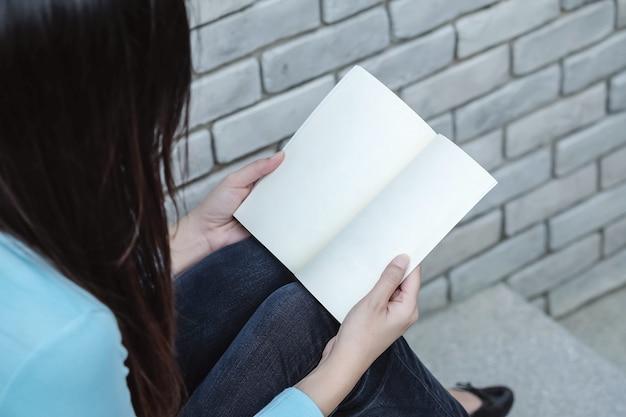 Donna del primo piano che si siede sulla scala di pietra per la lettura del libro nel tempo libero nel giardino