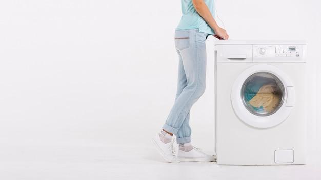 Donna del primo piano che si siede vicino alla lavatrice