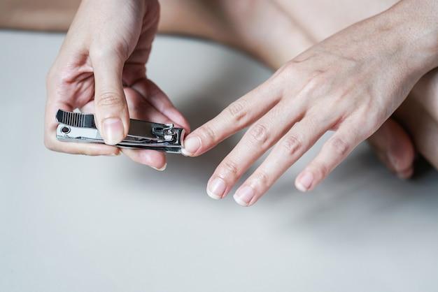 Donna del primo piano che taglia i suoi chiodi