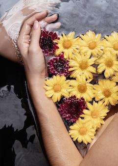 Donna del primo piano che tiene i fiori terapeutici