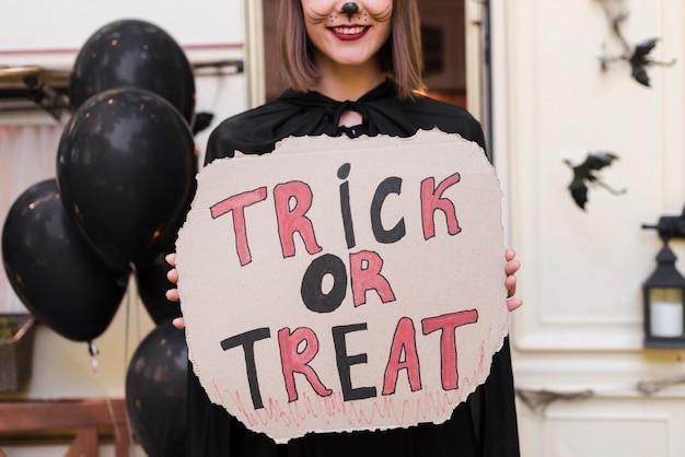Donna del primo piano che tiene il segno di halloween